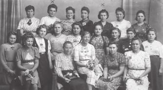 Mit diesen Frauen lebte Maria Koenig, die Mutter des Künstlers Robert Koenig, während der Zwangsarbeit zusammen in einer Baracke in Speyer. Maria Koenig ist auf dem Foto nicht zu sehen, weil sie zum Zeitpunkt der Aufnahme in der Fabrik arbeitete. Mit den herausgeputzten Frauen, die teilweise freundlich in die Kamera lächeln, wollten die Nazis das Rote Kreuz beeindrucken.
